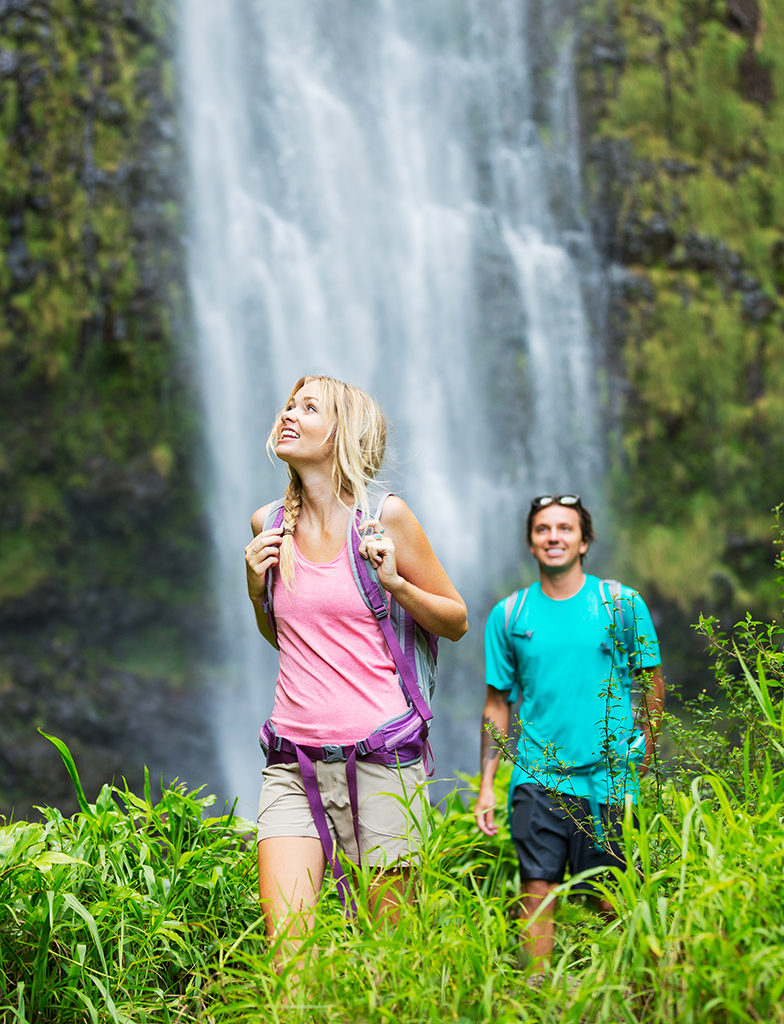 Couple hiking past a waterfall