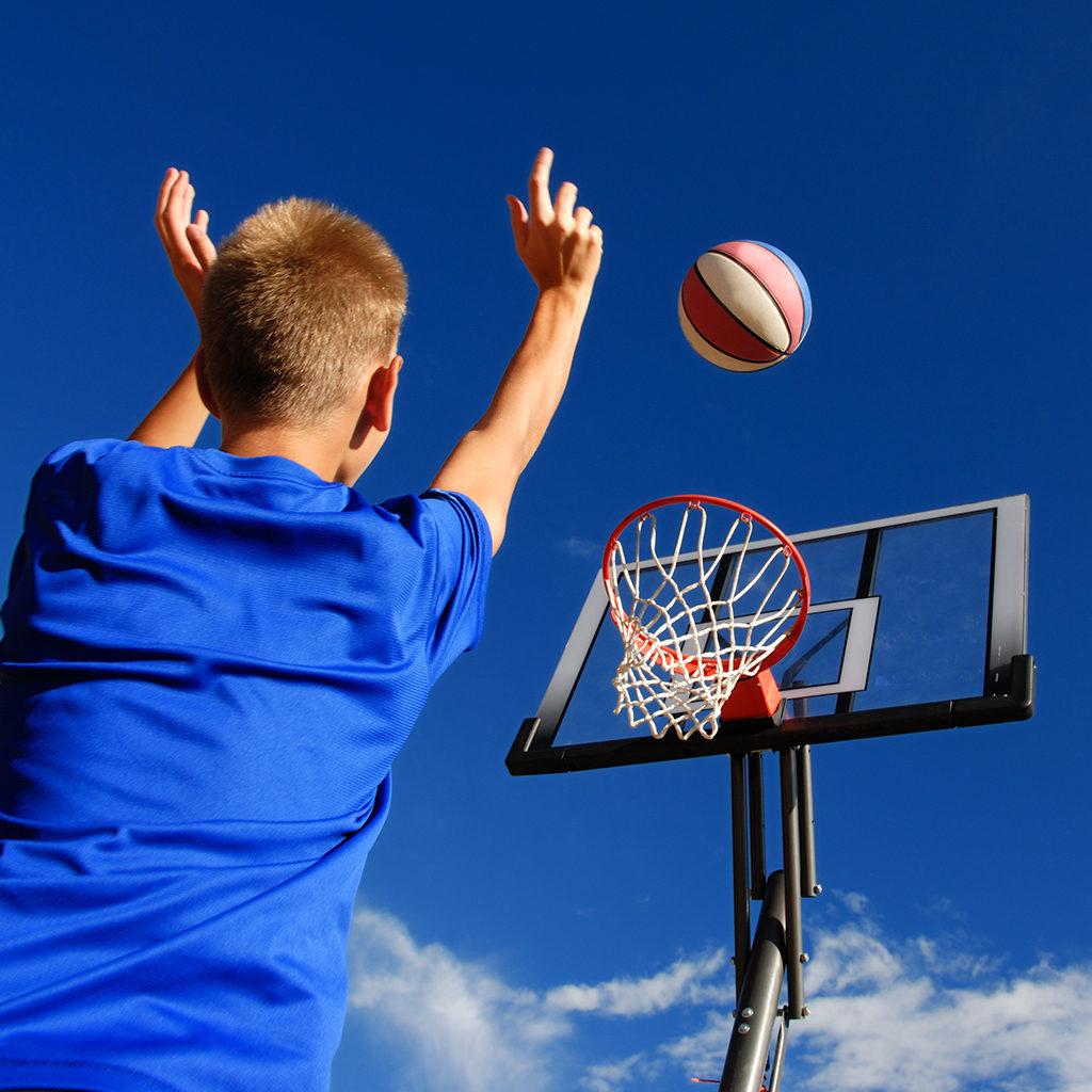 Boy shooting baskets outside