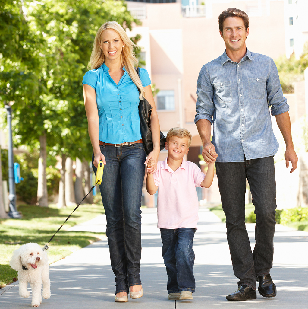 Father, mother, and son walk their dog along a sidewalk.
